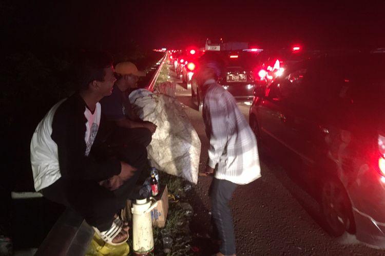 Pedagang asongan dan pemulung mengais rezeki dari kemacetan Tol Cipali, Sabtu (1/7/2017) malam.