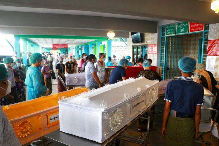 Orang-orang yang memakai masker menunggu saat peti mati berisi jenazah antri di luar krematorium di pemakaman Yay Way di Yangon, Myanmar, Rabu 14 Juli 2021.