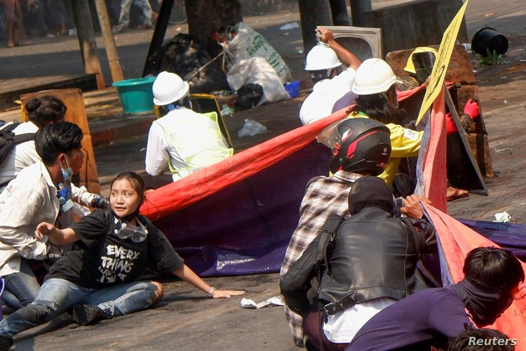 Protesters lie on the ground after police opened fire to disperse an anti-coup protest in Mandalay, Myanmar, (3/3/2021). Among them Angel, 19, bottom left, also known as Kyai Sin, took cover before she was shot in the head