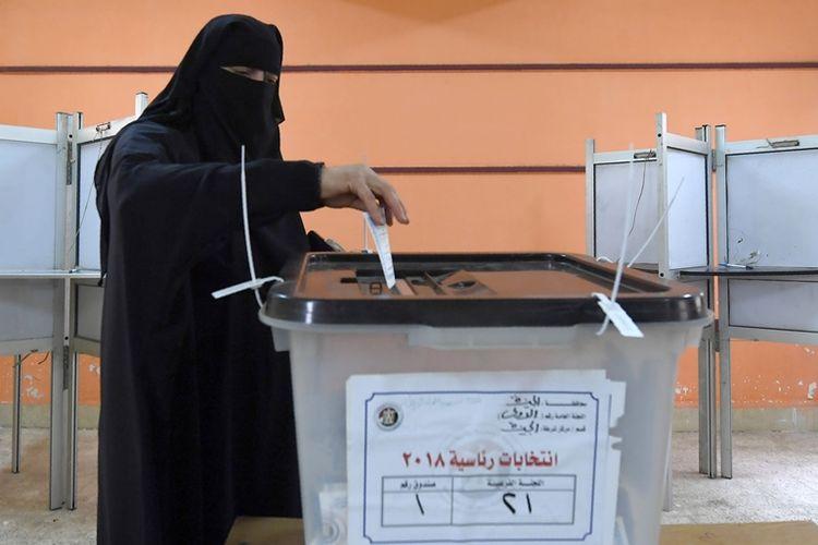Perempuan Mesir memasukkan surat suara dalam pemilu presiden hari ketiga di Giza, Rabu (28/3/2018).