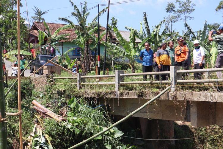 Jembatan Kali Bojong di Desa Pejawaran, Kecamatan Pejawaran, Kabupaten Banjarnegara, Jawa Tengah, miring akibat tiang jembatan ambruk tergerus arus sungai.