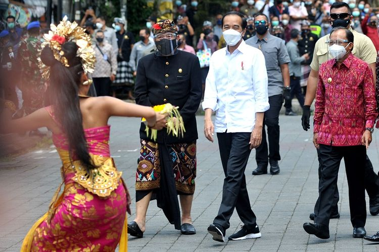 Presiden Joko Widodo (tengah) didampingi Gubernur Bali Wayan Koster (kanan) dan Wagub Bali Tjokorda Oka Artha Ardana Sukawati (kiri) disambut penari Bali saat akan meninjau proses vaksinasi COVID-19 di Puri Ubud, Gianyar, Bali, Selasa (16/3/2021). Kunjungan tersebut dilakukan Presiden Jokowi untuk melihat secara langsung proses vaksinasi secara massal kepada para pelayan publik, tokoh agama dan adat serta masyarakat setempat. ANTARA FOTO/Fikri Yusuf/rwa.