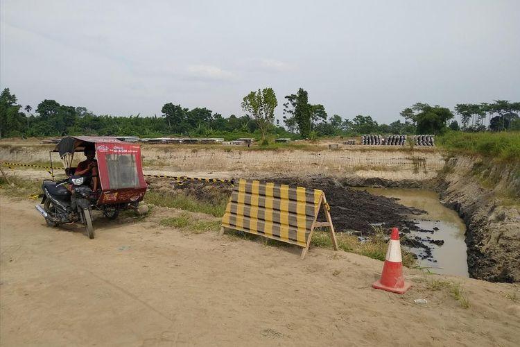 Seseorang di dalam becak motor memerhatikan galian untuk bendungan di Deli Serdang yang dibangun dengan tujuan mengaliri sekitar 4.500. Pengadilan Negeri Lubuk Pakam Batak mengeksekusi lahan ini karena adanya penolakan.