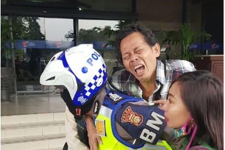 Masyarakat yang terkena serangan jantung di Halte TransJakarta, Jumat (14/2/2020) digendong oleh petugas kepolisian menuju RS Harapan Kita, Jakarta.