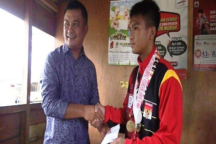 Mantan Bupati Nias Selatan, Idealisman Dachi, memberikan bonus Rp 3 juta kepada Eben Setiawan Harefa, peraih medali perak dati South East Asia Karate Federation (SEAKF), yang digelar di Semarang, awal Mei 2017.
