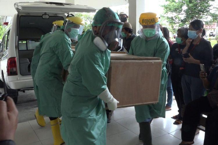 Petugas kamar jenazah RSUD Mimika menurunkan jenazah Oktovianus Rayo dari mobil jenazah, Sabtu (10/4/2021).