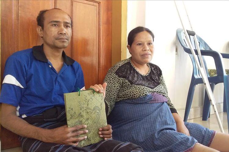 Foto : Suami Istri, Quido Van Areso dan Yoventa Timbu memegang tas berisi uang santuanan dari Presden Joko Widodo, Jumat (12/7/2019).