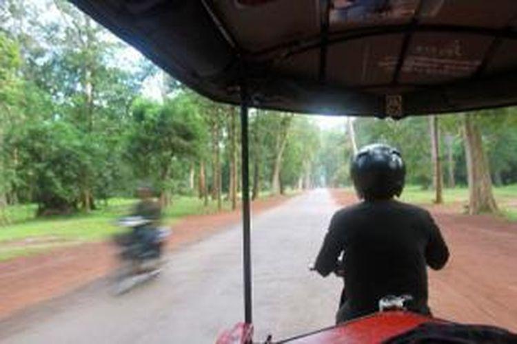 Sopir tuk-tuk mengemudi berkeliling kawasan Candi Angkor, Siem Reap, Kamboja. Tuk-tuk merupakan transportasi yang diandalkan untuk berwisata di kawasan Angkor karena luasnya kawasan Candi Angkor mencapai 200 kilometer persegi.