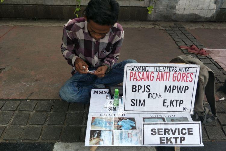 Tukang service kartu identitas di CFD Sudirman-Thamrin, Minggu (9/12/2018).