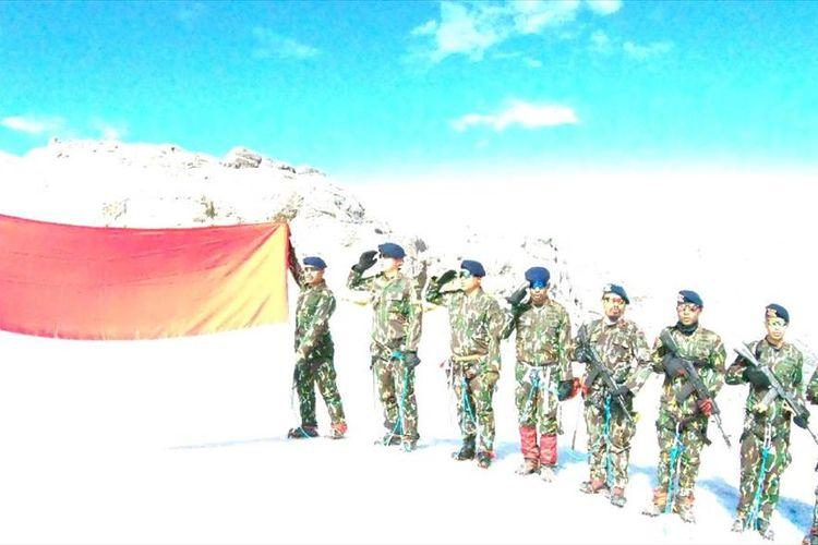 11 anggota Brimob Mimika saat membentangkan bendera merah putih di Puncak Cartenz, Papua.