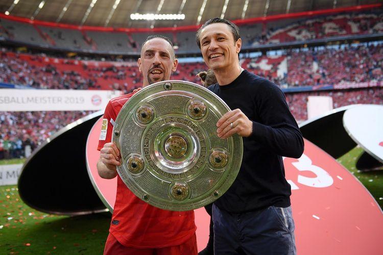 Franck Ribery dan Niko Kovac memamerkan trofi juara Liga Jerman seusai laga Bayern Muenchen vs Eintracht Frankfurt di Allianz Arena dalam pertandingan Bundesliga 1, 18 Mei 2019.