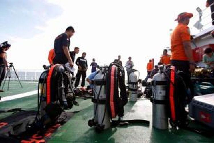 Tim penyelam dari Basarnas menyiapkan perlengkapan selam di atas kapal SAR KN101 Purworejo, di tengah perairan Pangkalan Bun, Kalimantan Tengah, Jumat (2/1/2015). Pencarian kembali mengalami kendala akibat ketinggian ombak mencapai hingga lima meter.