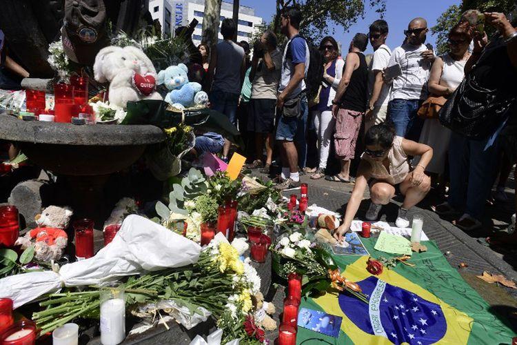 Seorang wanita meletakkan sesuatu di dekat karangan bunga, pesan-pesan, dan sejumlah mainan anak yang dipasang untuk mengenang serangan di Kota Cambrils, Spanyol pada Jumat (18/8/2017).