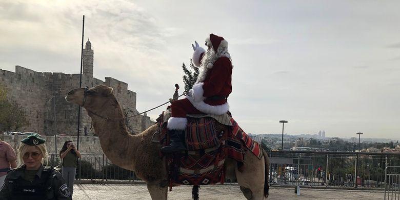 Mantan pemain basket, Issa Kassassieh, mengenakan kostum Sinterklas, dan menaiki unta menebarkan perayaan Natal di jalan-jalan Yerusalem (21/12/2017).