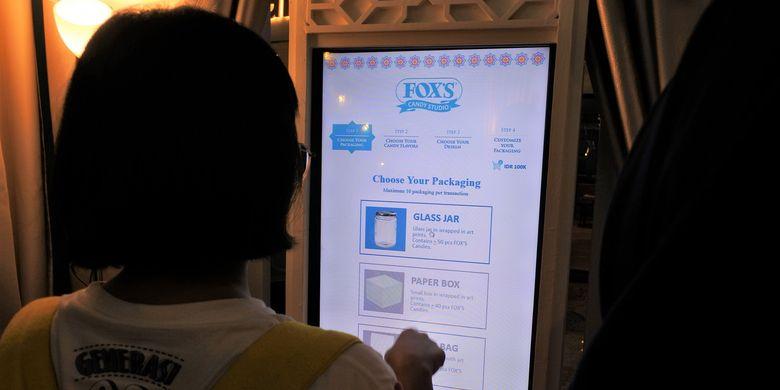 Pembeli dapat memilih varian rasa permen, pola desain kemasan, dan bentuk kemasan yang diinginkan melalui layar sentuh.