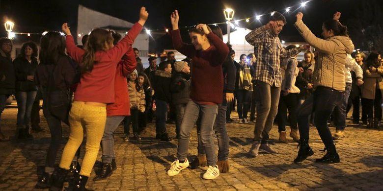 Anak-anak dan orang dewasa menari Murinheira, tarian tradisional asal Celtic, di desa Vale de Salgueiro, utara Portugal, pada epifani, Jumat (5/1/2018). (AP Photo/Armando Franca)