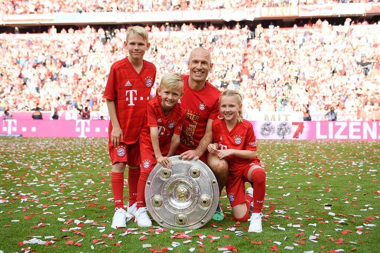 Arjen Robben bersama anak-anaknya memamerkan trofi piring salad, lambang gelar juara Liga Jerman, seusai laga Bayern Muenchen vs Eintracht Frankfurt di Allianz Arena dalam pertandingan Bundesliga 1, 18 Mei 2019.