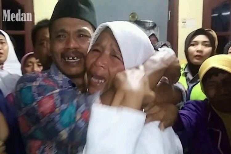 Ibu kandung Kompol Andi Chandra menangis histeris di pelukan kerabatnya saat melihat keranda jenazah anaknya tiba di rumah duka di Kecamatam Gunung Maligas, Kabupaten Simalungun, Minggu (22/4/2018).
