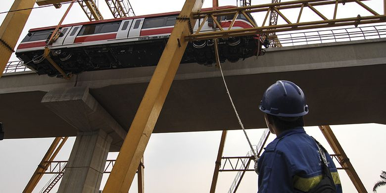 Karyawan mengawasi proses pengangkatan perdana kepala gerbong kereta layang ringan atau LRT ke atas rel di Stasiun Harjamukti, Depok, Jawa Barat, Minggu (13/10/2019). Progres pembangunan proyek LRT Jabodebek lintas pelayanan 1 Cibubur-Cawang telah mencapai 85,7 persen dan satu rangkaian gerbong LRT telah diangkat dan diparkir di Depo Stasiun Harjamukti.