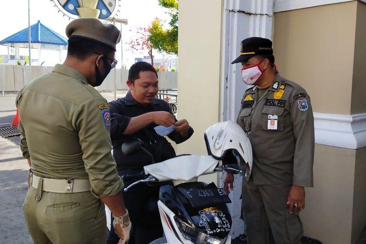Petugas Satpol PP memberikan masker kepada seorang PNS Pemkot Tegal yang kedapatan tidak memakai masker saat akan memasuki perkantoran di Balai Kota Tegal, Jawa Tengah, Kamis (10/9/2020)