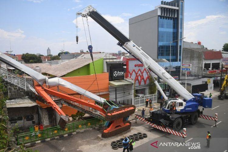 Petugas mengevakuasi ekskavator yang terguling menimpa tangga jembatan penyeberangan orang (JPO) di Kampung Melayu, Jakarta, Selasa (22/9/2020). Ekskavator milik Dinas Lingkungan Hidup (DLH) DKI Jakarta itu terguling dari atas mobil mobilisasi saat akan dikembalikan ke gudang.