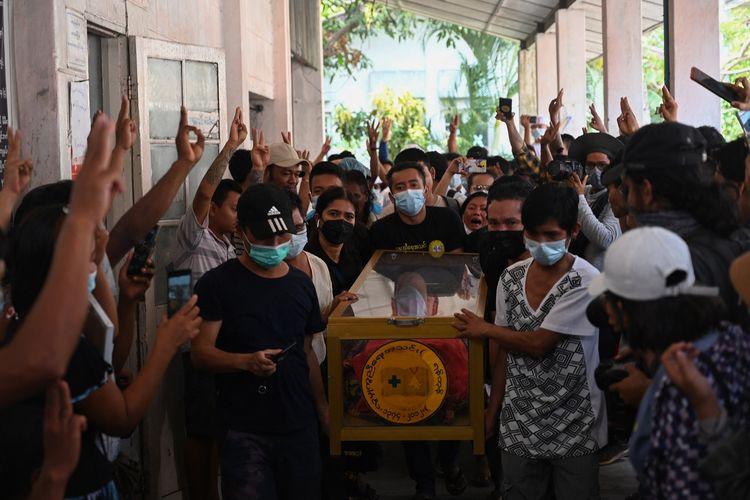 Jenazah demonstran yang tewas dibunuh dalam demonstrasi Myanmar diarak keluar dari rumah duka oleh keluarganya, dan disambut pengunjuk rasa lain sembari mengacungkan salam tiga jari di Yangon, pada 15 Maret 2021.