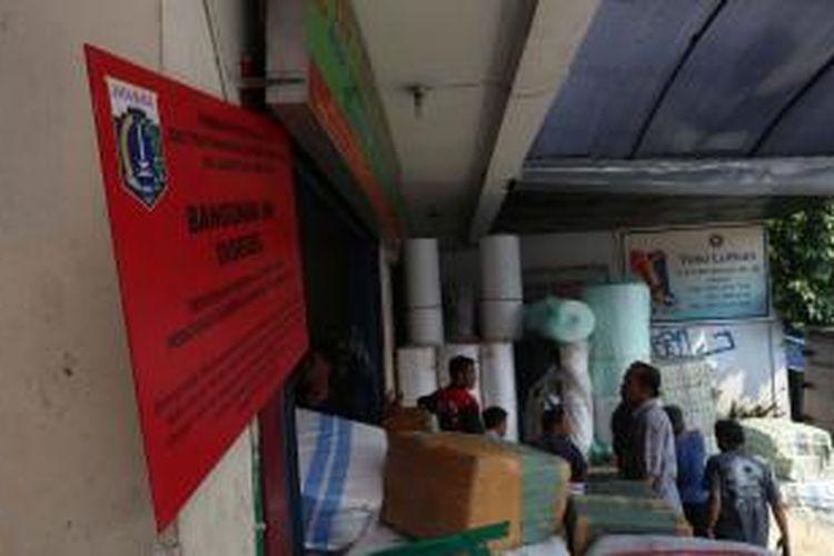 Sebuah kantor ekspedisi di Jalan KH Mas Mansur, Tanah Abang, Jakarta Pusat, tampak ada papan segel Pemprov DKI Jakarta, Kamis (11/7/2013). Penutupan dilakukan untuk mengatasi kemacetan lalu lintas akibat aktivitas bongkar muat di kantor tersebut.