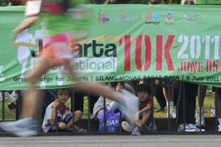 Warga melihat peserta lomba lari Jakarta International 10K 2011 yang akan memasuki garis finish di kawasan Monumen Nasional, Jakarta, Minggu (5/6/2011). Lomba lari menempuh jarak 10 kilometer ini diadakan untuk merayakan HUT Ke-484 Kota Jakarta.