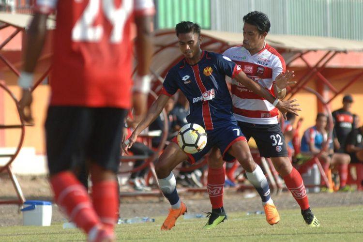 Bek Madura United, Benny Wahyudi berebut bola dengan pemain Selangor FA dalam laga ujicoba internasional di Stadion Gelora Ratu Pamelingan