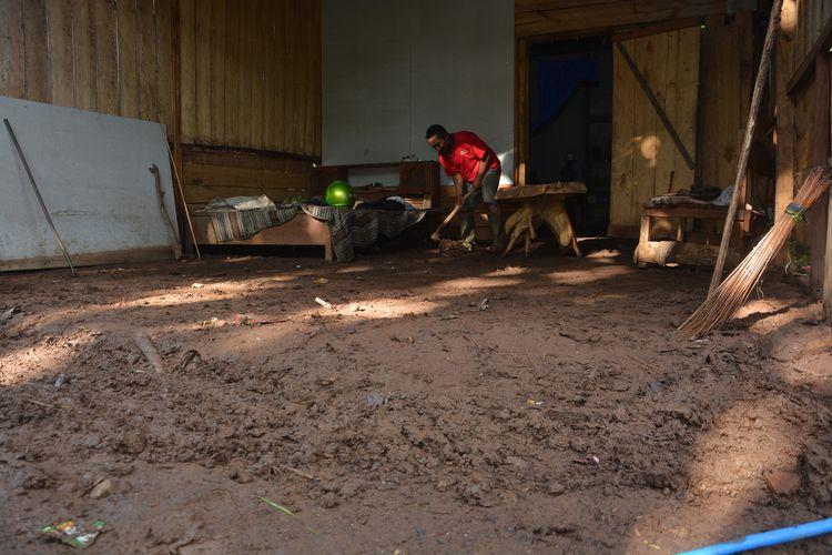 Kaspo, warga Desa Sumberjati, Kecamatan Jatirejo, Kabupaten Mojokerto, Jawa Timur, saat membersihkan sisa banjir bandang di rumahnya, Sabtu (8/2/2020).