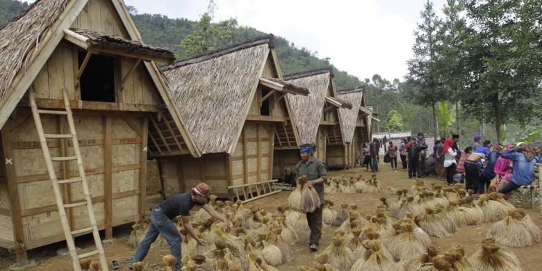 Warga adat Kasepuhan Ciptagelar, Kabupaten Sukabumi, Jawa Barat memasukkan padi ke dalam lumbung (leuit) komunal saat upacara seren taun, Minggu (24/8/2014). Seren taun adalah upacara adat untuk mensyukuri hasil panen padi selama satu tahun. KOMPAS IMAGES/KRISTIANTO PURNOMO