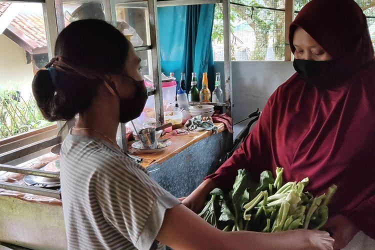 Merlin (24) menyerahkan sawi seberat dua kilogram hasil panennya kepada Nurlaela (35) Kamis (17/12/2020). Sawi itu ditukarkan dengan dua buah porsi bakso. Nurlaela merupakan salah satu pedagang bakso dan sembako yang melayani sistem barter sayuran. Keduanya merupakan warga Desa Nangka Kecamatan Kadugede, kabupaten Kuningan yang merintis sebagai Desa Agrobisnis.