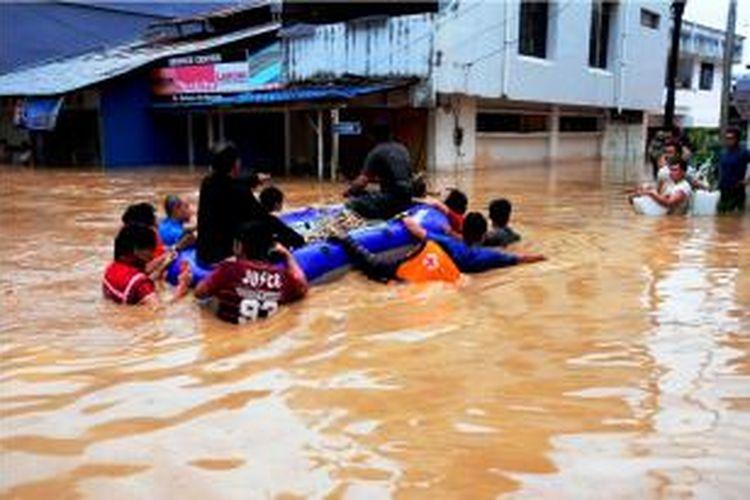 Foto yang diambil tanggal 15 Januari 2014 memperlihatkan tim SAR tengah mengevakuasi warga yang menjadi korban banjir di Manado, Sulawesi Utara menggunakan perahu karet.