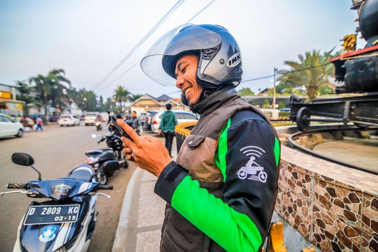 Ilustrasi driver Gojek sedang memegang handphone, menunggu order dari customer.