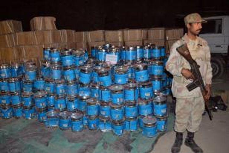Seorang prajurit paramiliter Pakistan menjaga barang bukti bahan peledak bom yang ditemukan di sebuah gudang di kota Quetta.