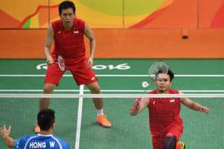 Pasangan ganda putra Indonesia, Mohammad Ahsan (kanan)/Hendra Setiawan, mengembalikan kok dari pemain China, Chai Biao/Hong Wei, pada babak penyisihan grup Olimpiade Rio 2016 di Riocentro Stadium, Rio de Janeiro, 13 Agustus 2016.