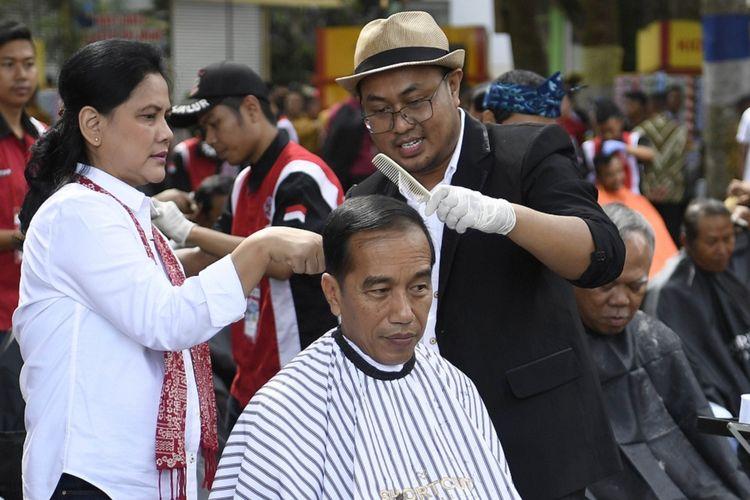 Presiden Joko Widodo (tengah) didampingi Ibu Negara Iriana Joko Widodo (kedua kiri) saat mengikuti potong rambut massal di area wisata Situ Bagendit, Garut, Jawa Barat, Sabtu (19/1/2019). ANTARA FOTO/Puspa Perwitasari/foc.