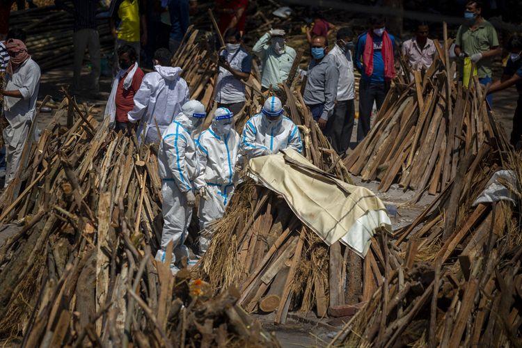 Orang-orang melakukan ritual di samping tumpukan kayu pemakaman anggota keluarga yang meninggal karena Covid-19 di tanah yang telah diubah menjadi krematorium kremasi massal korban Covid-19 di New Delhi, India, Sabtu, 24 April 2021.