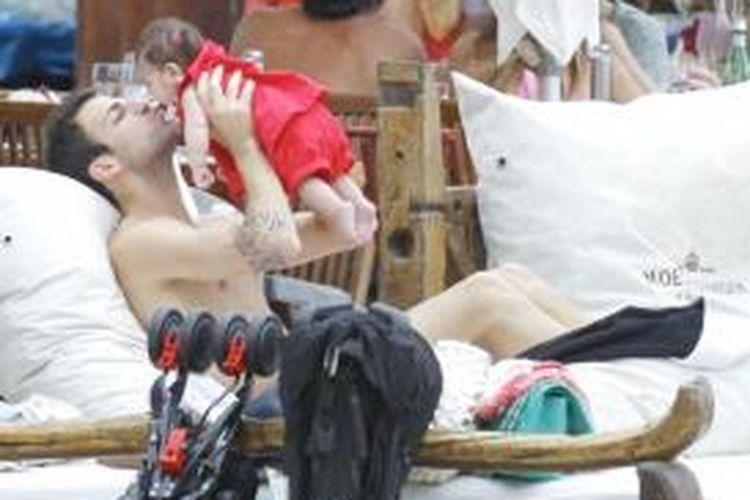 Gelandang Barcelona, Cesc Fabregas, bersama anaknya, Lia, saat berlibur di Ibiza, Spanyol, 4 Juli 2013.