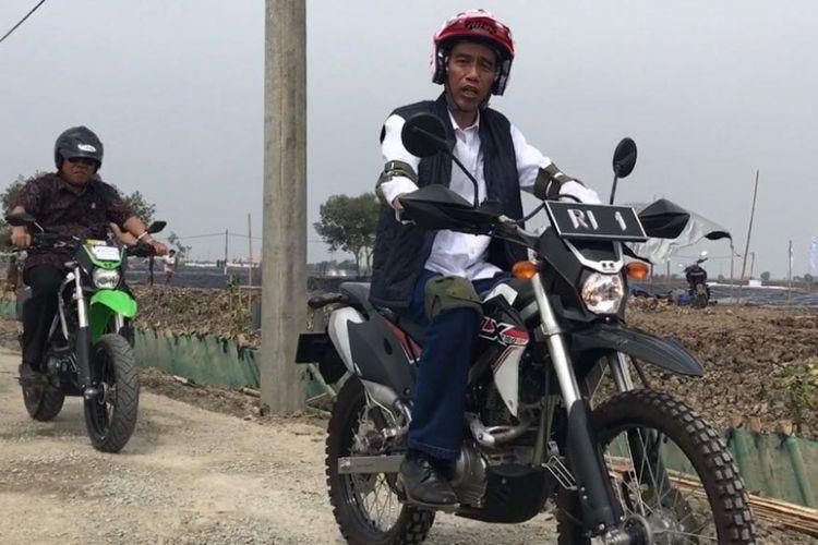 Presiden Joko Widodo mengendarai motor trail saat meninjau lokasi tambak udang dan ikan bandeng sebagai bagian dari program perhutanan sosial di Kecamatan Muara Gembong, Bekasi, Rabu (1/11/2017).
