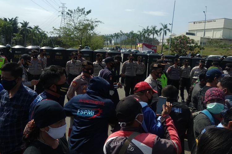 Puluhan personel kepolisian menyekat jalan di salah satu kawasan industri di Kabupaten Bekasi, Jawa Barat, yang menjadi rute buruh menuju DPR RI.