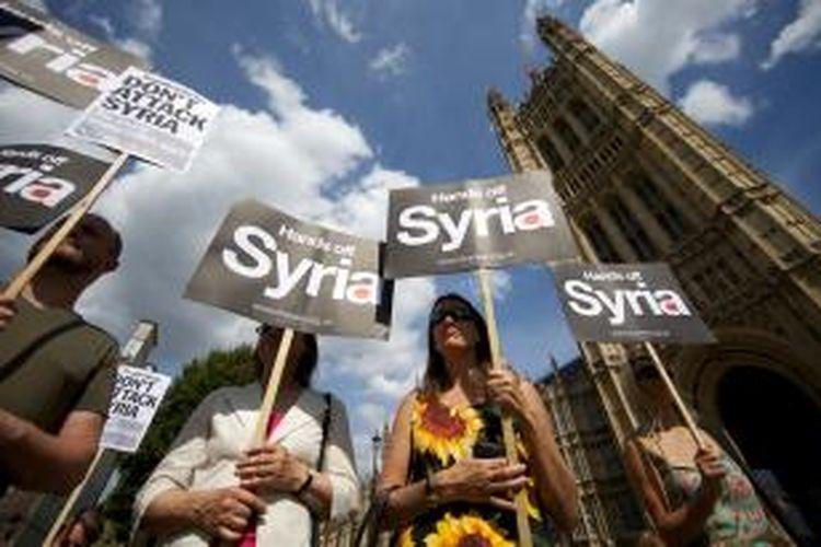 Sejumlah warga Inggris menggelar demonstrasi, Kamis (29/8/2013), menolak keterlibatan negara tiga singa itu dalam aksi militer ke Suriah, terkait dugaan penggunaan senjata kimia oleh rezim Bashar al Assad pada serangan Rabu (21/8/2013). Pada hari yang sama, parlemen Inggris menolak mendukung keterlibatan Inggris dalam aksi militer ke Suriah, dengan suara 285 berbanding 272.