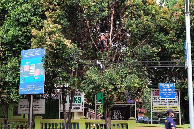 Seorang pria tanpa identitas di Depok, Jawa Barat menyita perhatian warga karena tiba-tiba memanjat pohon sambil berteriak-teriak di depan SD Anyelir 1, Jalan Nusantara Raya, Pancoran Mas, Selasa (27/10/2020) petang.