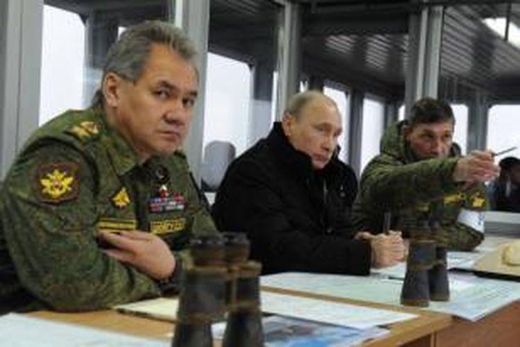 Menteri Pertahanan Rusia, Sergei Shoigu (kiri) saat mendampingi Presiden Vladimir Putin ketika meninjau latihan perang Rusia belum lama ini. Menhan Shoigu terancam terkena larangan bepergian ke Uni Eropa dan AS sebagai bagian dari sanksi Barat terhadap Rusia.