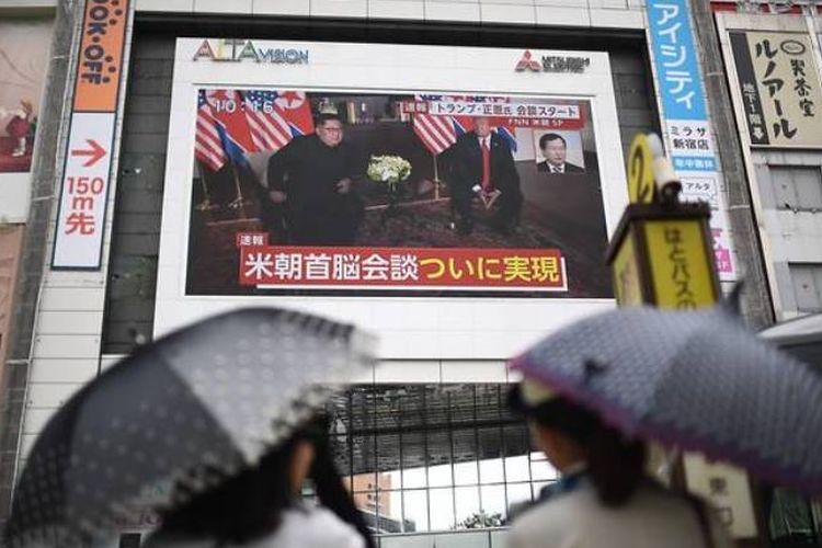 Pejalan kaki di Jepang berhenti di depan layar besar yang menyiarkan siaran langsung pertemuan Presiden AS Donald Trump dengan Kim Jong Un.