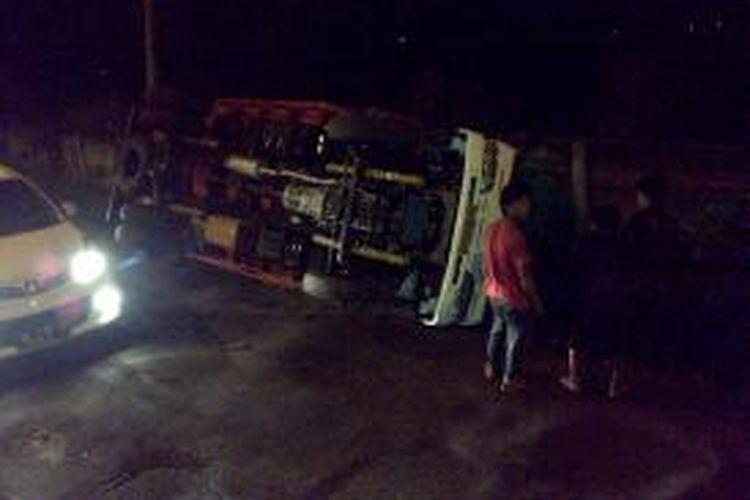 Sebuah truk sarat muatan terguling di samping Fly Over Sultan Agung Bandar Lampung, Senin (5/1) malam. Jalan bergelombang membuat truk pengangkut pakan ikan itu terguling.