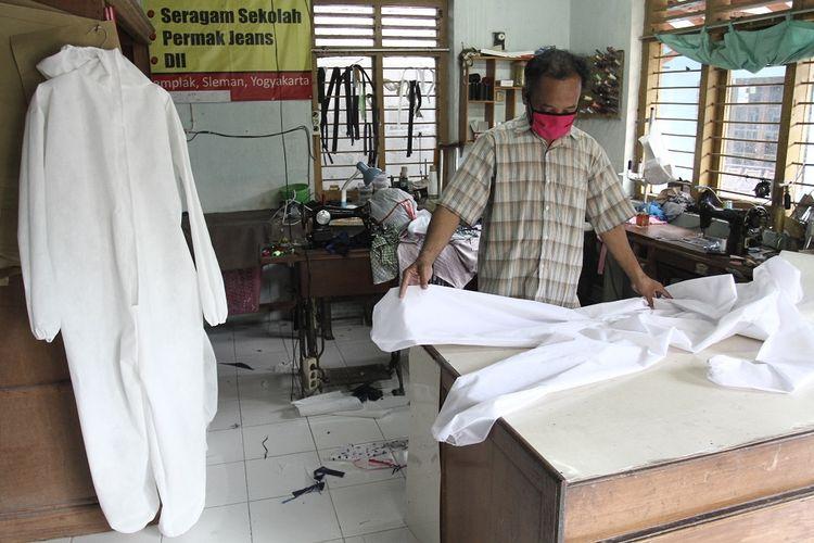 Iswanto (43) penjahit difabel menyelesaikan pembuatan pakaian hazmat di Desa Tonggalan, Wedomartani, Ngemplak, Sleman, DI Yogyakarta, Kamis (26/3/2020). Pembuatan pakaian hazmat atau perlengkapan dari Alat Pelindung Diri (APD) untuk tenaga medis pesanan salah satu rumah sakit di Yogyakarta tersebut sudah sesuai dengan standart keamanan Gugus Tugas Penanggulangan COVID-19. ANTARA FOTO/Hendra Nurdiyansyah/hp.