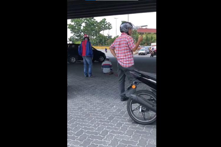 Tangkapan layar dari video orang shalat di tengah jalan sampai dijaga para pengendara motor. Peristiwa ini terjadi di Malaysia pada Kamis (25/2/2021) dan viral di media sosial.