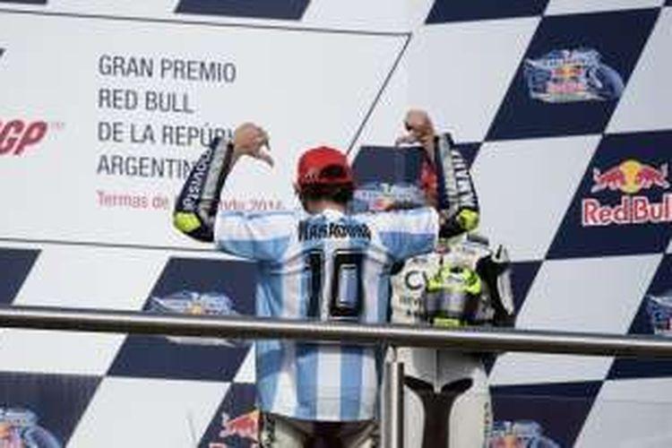 Pebalap Movistar Yamaha asal Italia, Valentino Rossi, merayakan kemenangan pada GP Argentina di Autodromo Termas de Rio Hondo dengan mengenakan baju bernomor punggung 10 milik legenda sepak bola Diego Maradona, Minggu (19/4/2015).