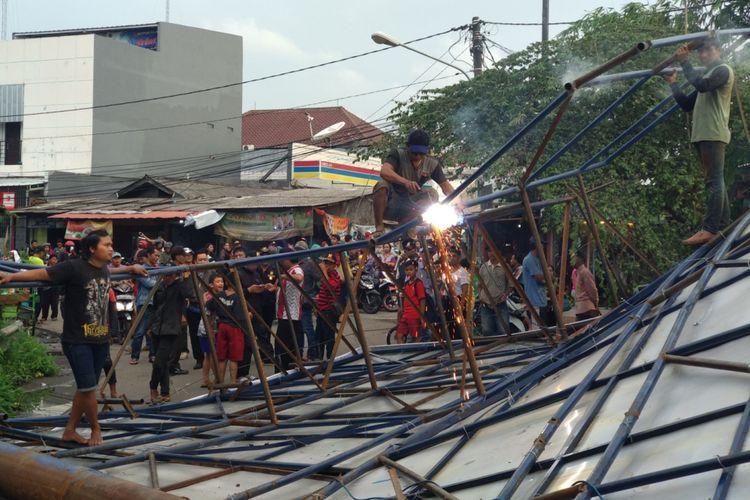 Petugas reklame kota Bekasi memotong besi reklame yang roboh menimpa jalan di Jatibening, Senin (19/2/2018)